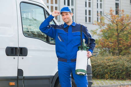 exterminator: Portrait of happy pest control worker wearing cap while standing against truck