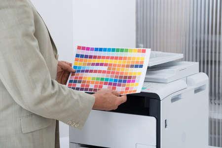fotocopiadora: Sección media de hombre de negocios que sostiene el papel de varios colores según la impresora en la oficina