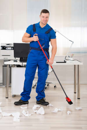office man: Full length portrait of smiling janitor holding broom while standing in office
