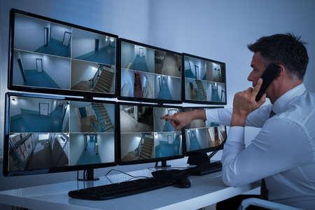 Vista lateral del operador de sistema de seguridad con walkie-talkie mientras observa imágenes de CCTV