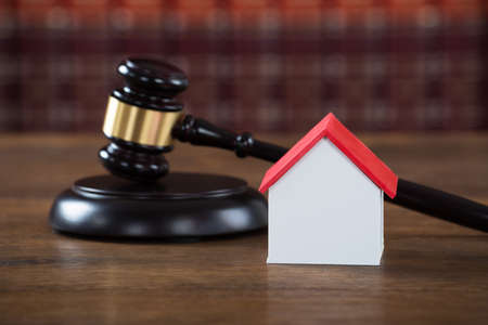 verdicts: Closeup of wooden mallet with house model on table in courtroom