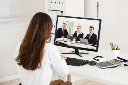 attending: Rear view of young businesswoman attending video conference on computer in office