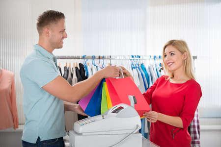 Gelukkig vrouwelijke klant die boodschappentassen van verkoper bij teller in kledingwinkel