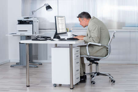 Side view of concentrated businessman using computer at desk in office Stock Photo