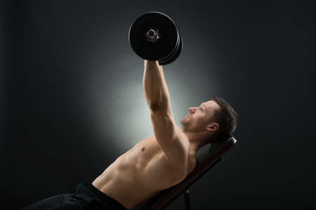 reclining chair: Determined mid adult man lifting dumbbells while reclining on chair against black background Stock Photo