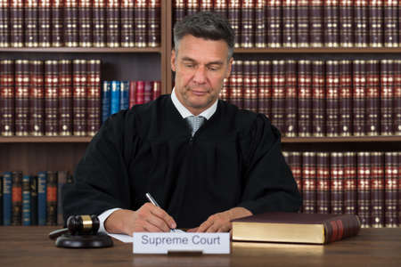 proceeding: Mature male judge writing on paper at table in courtroom Stock Photo