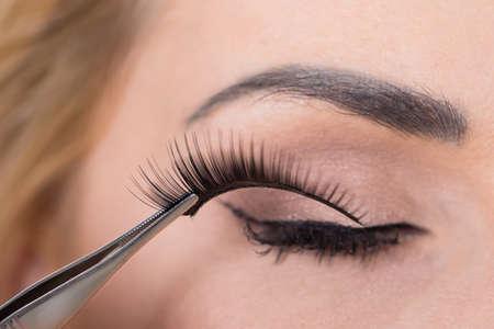 Close-up of false eyelashes being put on woman's eye 스톡 콘텐츠