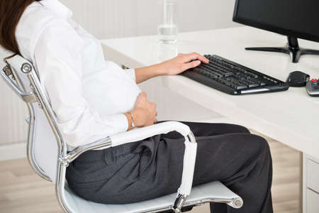 Office women: Side view midsection of pregnant businesswoman using computer at desk in office