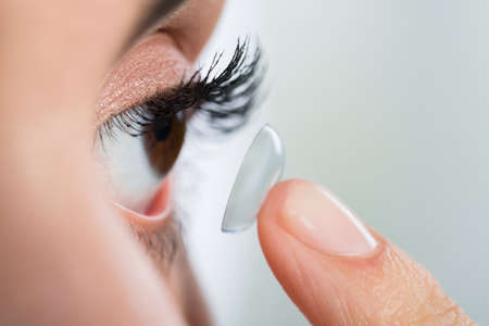 contact: Closeup of young woman wearing contact lens at home Stock Photo