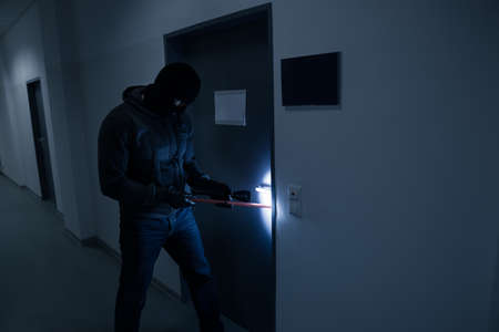 felon: Full length of thief with flashlight trying to break office door with crowbar