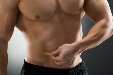 pinch: Midsection of muscular man holding fat belly against black background