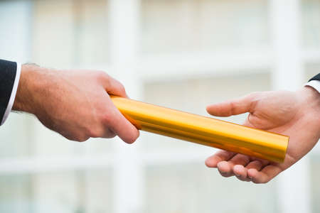 Cropped hand of businessman giving golden relay baton to colleague outdoors