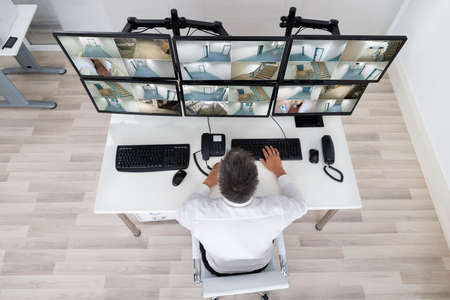 Rear view of security system operator looking at CCTV footage at desk in office Stock Photo