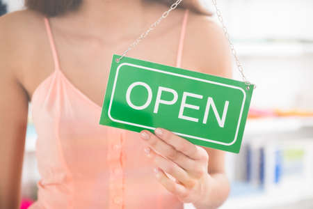 open sign: Midsection of female owner holding open sign in clothing store Stock Photo