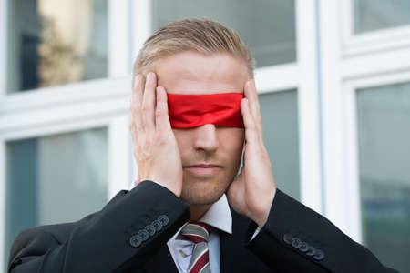 Jonge zakenman wat betreft rode blinddoek terwijl je tegen venster in openlucht