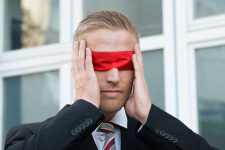 blindfold: Young businessman touching red blindfold while standing against window outdoors Stock Photo