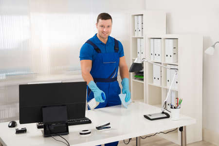 mid adult male: Mid adult male worker cleaning computer desk with spray and sponge at office