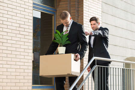 belongings: Side view of businessman firing employee carrying box with belongings outside office Stock Photo