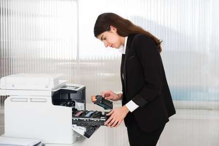 Side view of young businessman fixing cartridge in printer machine at office