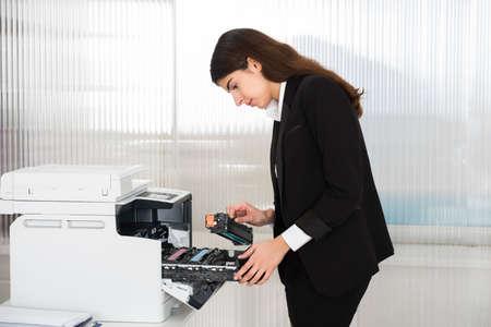 Vista lateral del hombre de negocios joven que se fijan en el cartucho de impresión del equipo en la oficina