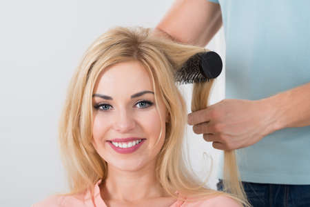 hairstylist: Male hairstylist brushing womans hair at salon Stock Photo