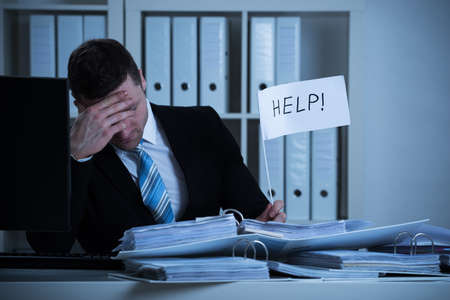 Stressed accountant holding help sign at desk while working late in office