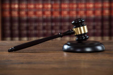 proceeding: Closeup of wooden mallet on table in courtroom