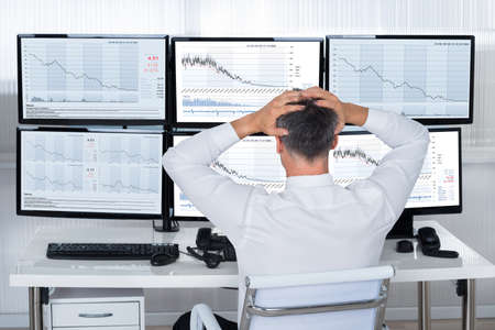 Rear view of stock trader with hands on head looking at graphs on screens Stockfoto