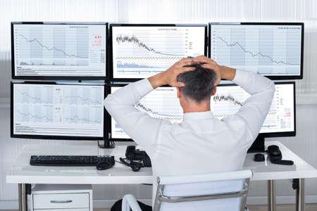 Rückansicht der Aktienhändler mit den Händen auf dem Kopf auf Graphen auf Bildschirmen suchen Standard-Bild