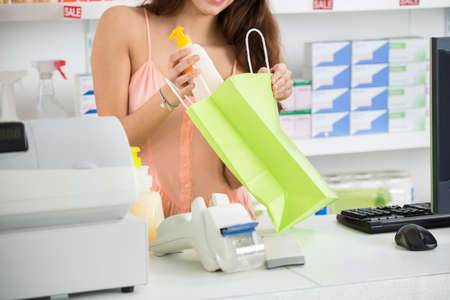 checkout counter: Midsection of young saleswoman putting cleansing product into paper bag at checkout counter in supermarket