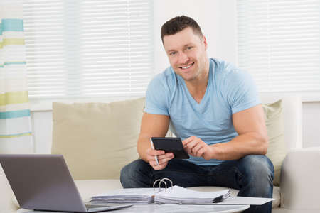 home finances: Mid adult man calculating home finances at table