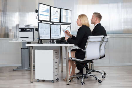 multiple: Financial workers analyzing data displayed on computer screens at desk in office Stock Photo