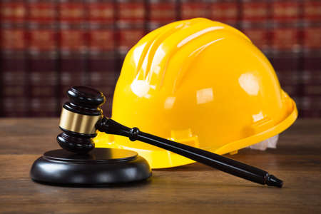 Closeup of wooden mallet and yellow hardhat on table in courtroom Stockfoto