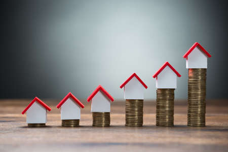Huis modellen gerangschikt op gestapeld munten op tafel tegen een grijze achtergrond Stockfoto