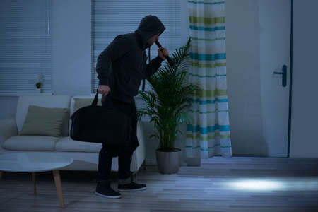 intruding: Full length of robber with flashlight and bag walking in living room Stock Photo