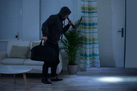 Longueur totale du voleur avec une lampe de poche et un sac marche dans le salon Banque d'images