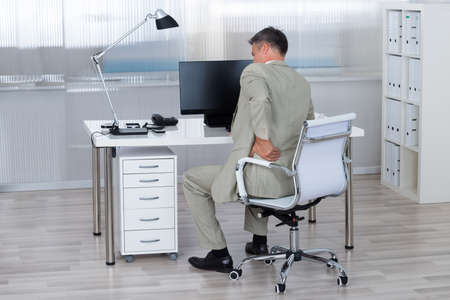 back to work: Rear view of businessman suffering from backache on chair in office