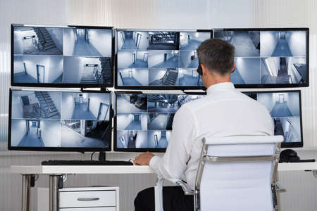 Rear view of security system operator looking at CCTV footage at desk in office Standard-Bild