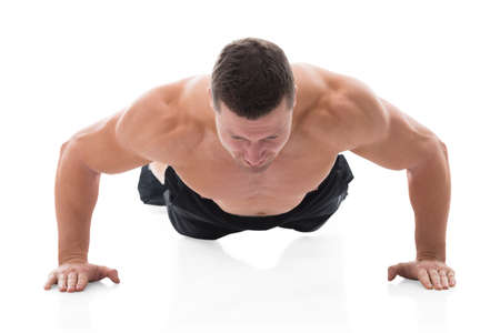 mid thirties: Determined muscular man doing push ups against white background