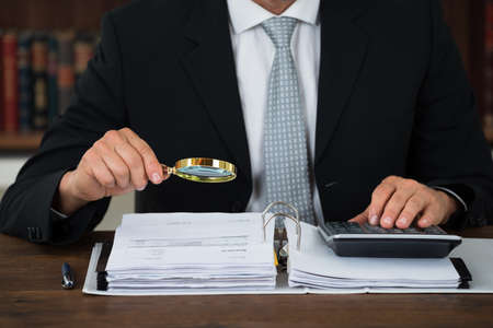 Midsection of male accountant scrutinizing financial documents at table in office
