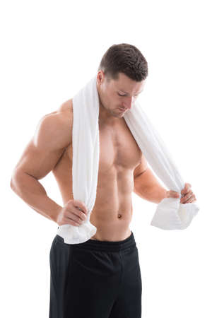 white towel: Strong man holding towel around neck while standing against white background Stock Photo