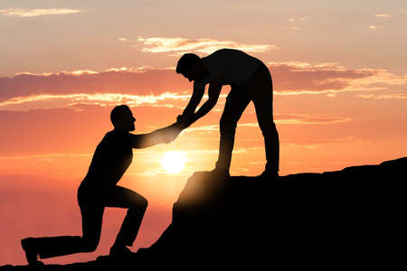helping: Silueta del hombre joven que ayudar un amigo del varón en la escalada en roca durante el atardecer