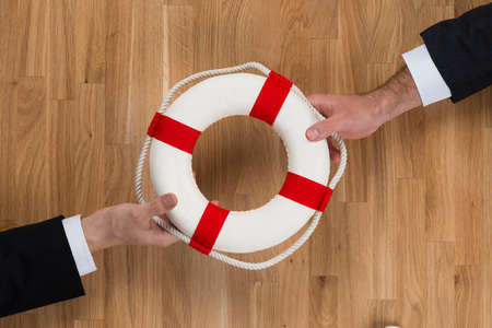 business survival: Cropped image of businessmen passing lifebuoy over wooden table Stock Photo