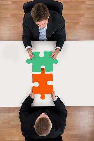 representing: Directly above shot of businessmen assembling jigsaw puzzle representing teamwork at desk
