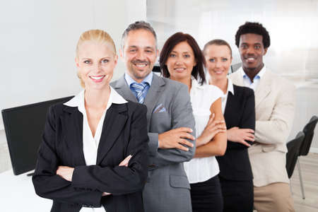 Portrait of multiethnic team with arms crossed smiling in office photo