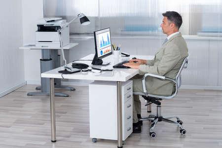 ビジネスマンのオフィスでの机にコンピューターを使用しての完全な長さ側面図