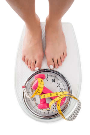 directly: Directly above shop of woman stepping on weight scale with dumbbells on white background Stock Photo