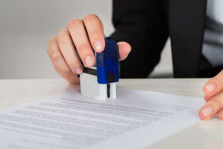 signing authority: Cropped image of young businesswoman stamping contract document at office desk Stock Photo