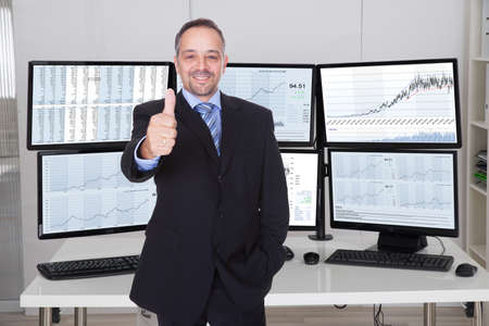 Portrait of stock market broker gesturing thumbs up against multiple monitors in office photo
