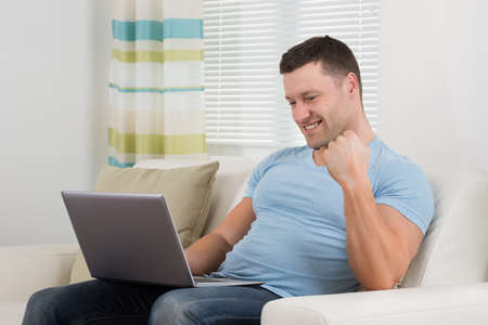clenching fists: Smiling mid adult man clenching fist while using laptop on sofa at home Stock Photo